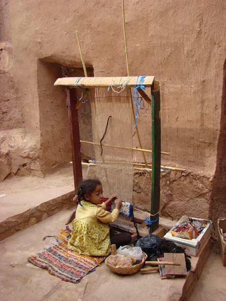 """Young girl working fairtrade Young girl working on a loom in Aït Benhaddou, Morocco in May 2008"" - image is courtesy of NationMaster.com"